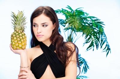 žena s ananásom v ruke